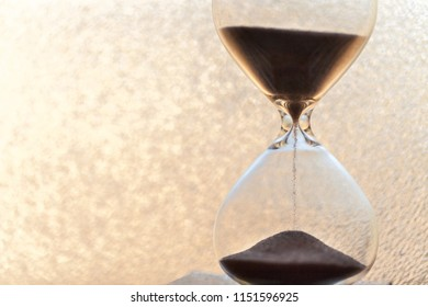 Sand running through the bulbs of an hourglass measuring the passing time in a countdown to a deadline, on a bright obscure glass background with copy space.