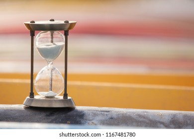 Sand running through the bulbs of an hourglass measuring the passing time in a countdown to a deadline, on a colorful kayaks background. Concept for vacation countdown. Time for relaxation.