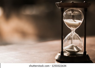 Sand running through the bulbs of an hourglass measuring the passing time in a countdown to a deadline, on a dark wooden background with copy space.