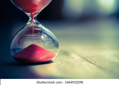 Sand running through the bulbs of an hourglass measuring the passing time in a countdown to a deadline, on a wooden floor background with copy space.