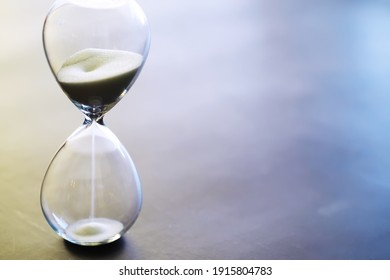 Sand running through the bulbs of an hourglass measuring the passing time in a countdown to a deadline, on a dark floor background with copy space.