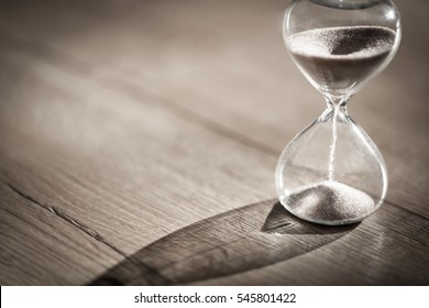 Sand running through the bulbs of an hourglass measuring the passing time in a countdown to a deadline, on a bright wooden background with copy space.