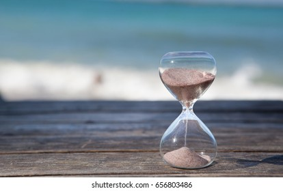 Sand running through the bulbs of an hourglass measuring the passing time in a countdown to a deadline. Beach and sea background, concept for vacation countdown. Time for relaxation.
