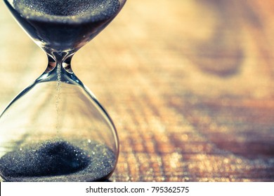 Sand running through the bulbs of an hourglass measuring the passing time in a countdown to a deadline, on a wooden background with copy space.