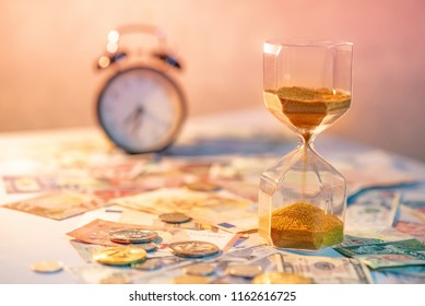 Sand running through the shape of hourglass on table with banknotes and coins of international currency. Time investment and retirement saving. Urgency countdown timer for business deadline concept