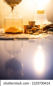 Sand running through the shape of hourglass with banknotes and coins stack of international currency on table. Time investment. retirement saving. Urgency countdown timer for business deadline concept