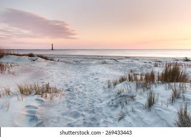 Sand and sea grasses on Folly Beach near Morris Island Lighthouse in Charleston, South Carolina.