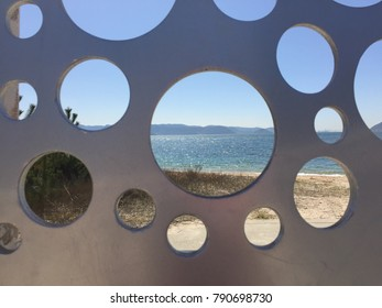 Sand, sea, and steel. The view Setouchi sea framed by grey steel installation. Naoshima, Japan.