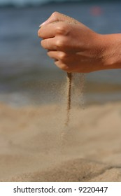 sand strews from woman's fist