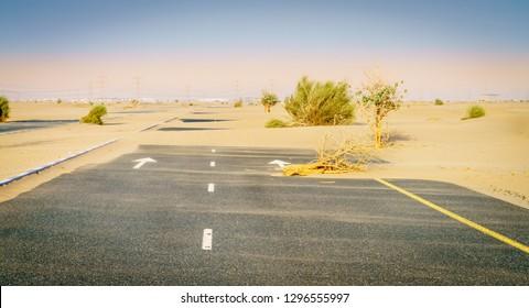 Sand is taking over a desert road near Dubai in UAE.