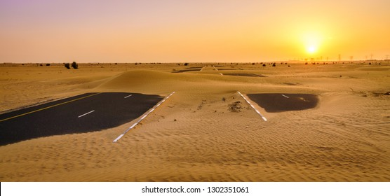 Sand is taking over a desert road near Dubai in UAE.