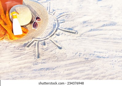 Sand texture (background) with hat, towel, sunscreen (suncream), sunglasses on the beach. The sun drawing in the sand. The empty pattern for  message. Summer vacations concept. Copy space.