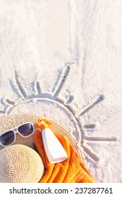 Sand texture (background) with hat, towel, sunscreen (suntan lotion, suncream), sunglasses on the a beach. The sun drawing in the sand. The empty pattern for message. Summer vacations. Copy space.