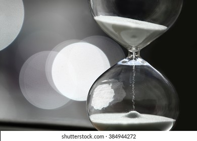 Sand Timer with white sand. With beautiful bokeh background.