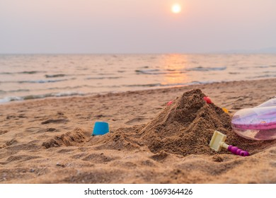 Sand and toys on the beach background, sunset time in the sea, summer beach concept.