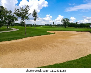 sand trap in golf course fairway with blue sky background