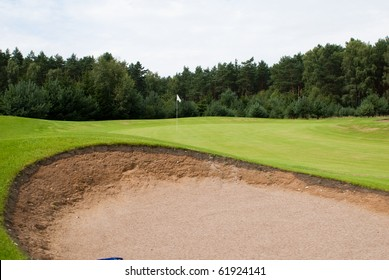 Sand trap and putting green with flag at golf course
