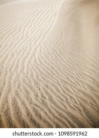 sand and wind patterns on dune surface. Pattern is formed by two types of sand grains - dark, small and lightweight and larger lighter and heavier ones. Maspalomas, Gran Canaria, Canary Islands, Spain