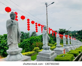 Sandakan, Sabah, Malaysia - February 06, 2019 : Statue at Puu Jih Shih Temple at Cecily Road in Sandakan, Sabah with decorations for Chinese New Year in the background