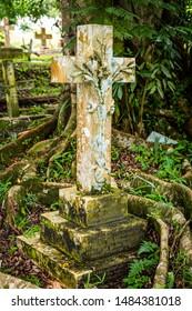 Sandakan, Sabah, Malaysia - February 10 2013: Historical Christian Cemetery Sandakan (founded 1883) in Sandakan, Sabah, Malaysia. Tombstone with floral relief of Frank Hatton, Mineralogist & Explorer