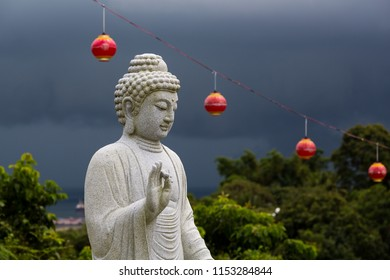 Sandakan, Sabah, Malaysia - January 2 2014: Statue at Puu Jih Shih Temple while a thunderstorm is approaching from Sandakan Bay