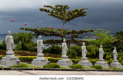 Sandakan, Sabah, Malaysia - January 2 2014: Statues at Puu Jih Shih Temple while a thunderstorm is approaching from Sandakan Bay