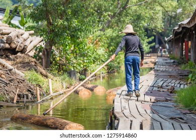 Sandakan, Sabah - March 28 2016: A man is floating timber logs to the feeding pool of a plywood factory