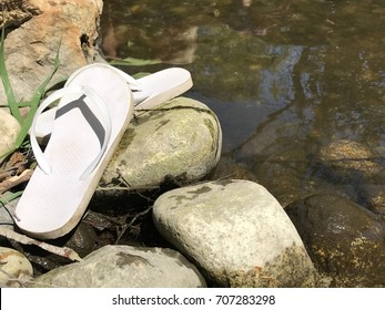 Sandals along the river bank with rocks
