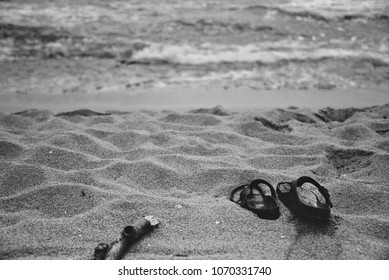 Sandals on a beach with blurry waves in the background.