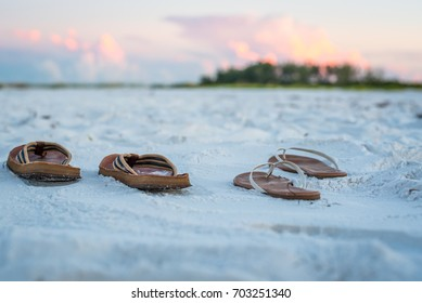 Sandals on the Beach Sand  at Sunrise