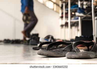 Sandals outside the main entrance of a mosque with a prayer taking off his shoes as blur background in Male, Maldives.