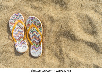 Sandals, shoes on the background of yellow beach sand. Colorful picture in warm colors. Sandals on the left side.
