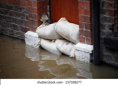 Sandbag barrier in doorway of flooded street in York.