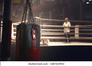 a sandbag hanging in front of a boxing ring have a janitor was cleaning