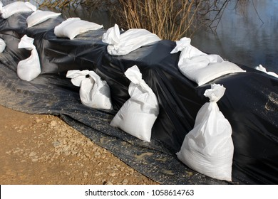 Sandbags flood protection on sand and rock foundation holding back water from flooded river covered with black nylon and sandbags on top with river and dried branches in background