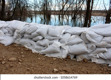 Sandbags flood protection on sand and rock foundation holding back water from flooded river with dried trees and cloudy sky at sunset in background