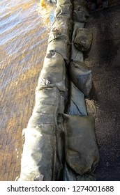 Sandbags keep the water on one side of a temporary embankment.