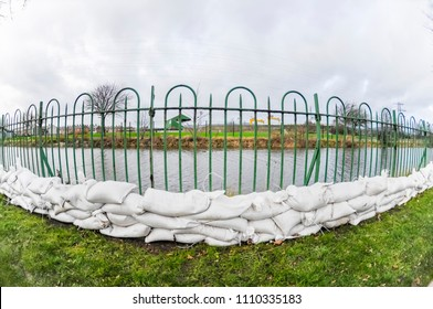 Sandbags are placed beside a river about to burst its banks