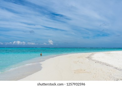 Sandbank with an unrecognized young woman in background in Maldives.
