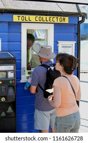 Sandbanks, Dorset, England - June 02 2018: Man and woman queueing in line at the ticket or toll collector booth for the Sandbanks to Shell Bay Chain Ferry which crosses the entrance of Poole Harbour