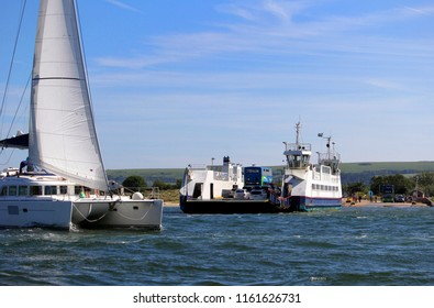 Sandbanks, Dorset, England - June 02 2018: A sailing catamaran passes the Sandbanks Chain Ferry which crosses the entrance of Poole Harbour
