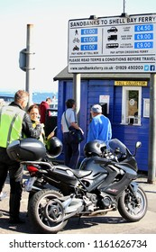 Sandbanks, Dorset, England - June 02 2018: Motorcyclists and pedestrians at the ticket or toll collector booth for the Sandbanks to Shell Bay Chain Ferry which crosses the entrance of Poole Harbour