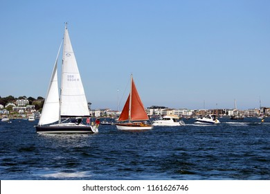Sandbanks, Dorset, England - June 02 2018: Two sailing boats, and two motor boats, sailing through Poole Harbour in line, on a clear sunny summer day, with the luxury Sandbanks houses in the distance