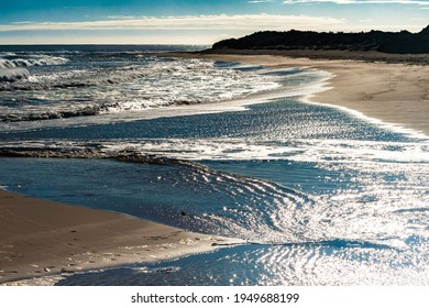 Sandbar at rivermouth with waves breaking through and flow to sea - Shutterstock ID 1949688199