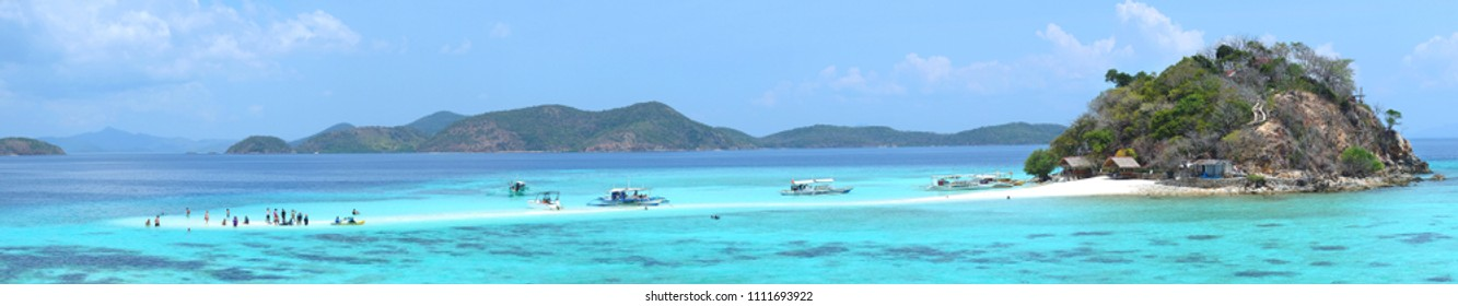Sandbar with tourists and boats on the tropical Bulog Uno island, Palawan, Philippines