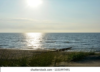 Sandbeach with marsh grass and wooden stages on the North Sea at sunset
