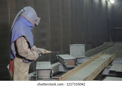 Sandblast. An employee prepares a metal part for painting. A harsh man works in the factory. A man in a protective form. Sparks fly