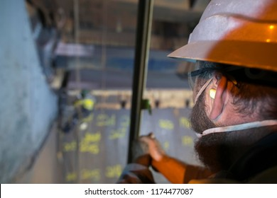 Sandblaster inspector construction worker standing wearing ears plug noise protection while inspecting rope access worker wearing safety equipment harness working at height abseiling sandblasting