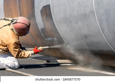 The sandblaster is sanding to steel pipe material. Abrasive blasting, more commonly known as sandblasting, is the operation of forcibly propelling a stream of abrasive material against a surface .