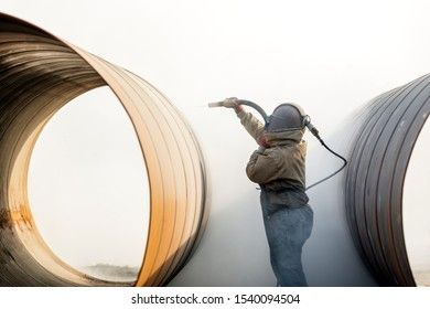 Sandblasting or abresive blasting for steel pipes before painting and coating.